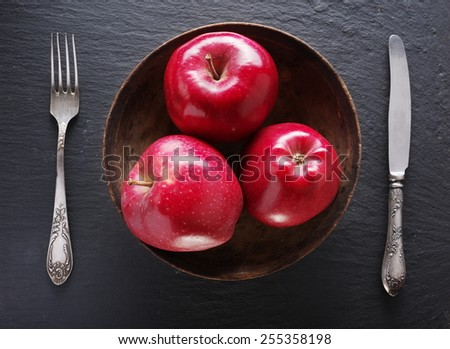 Red apples and table settings on a grey background. - stock photo