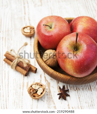 Red apples and walnuts  on old wooden table