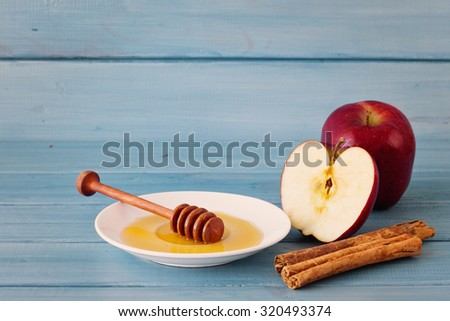 Red apples, cinnamon sticks and honey over a dish