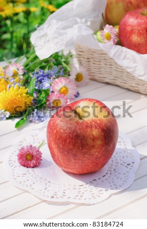 Red apples, flowers and basket on white garden table in sunny summer day