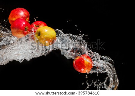 Red apples, flying in space with the water on a black background - stock photo