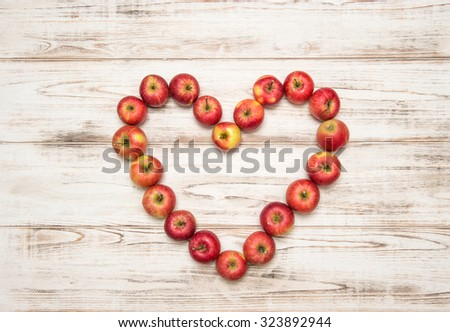 Red apples heart over rustic wooden background. Love concept - stock photo