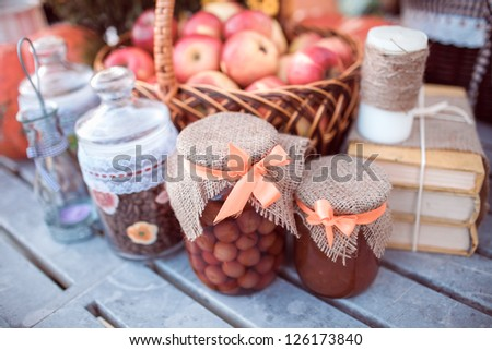 Red apples in basket, jars, jam and books on garden table - stock photo