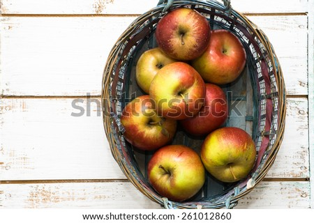 Red apples in basket on brown wooden background - stock photo