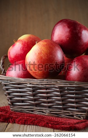 Red apples in basket with napkin on rustic wood. - stock photo