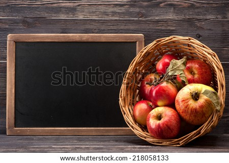 Red apples in basket with space for text on chalkboard