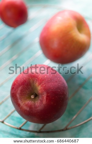 Red apples on a turquoise background. Vertical orientation. Selective focus.