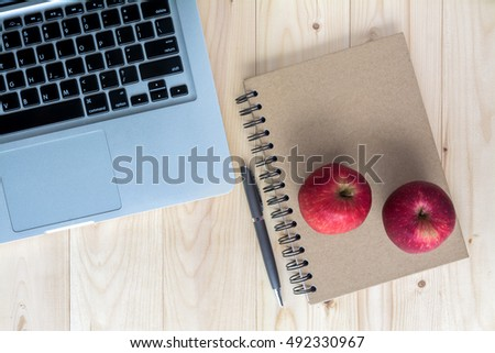 red apples on notebook and laptop, pen with light wooden background
