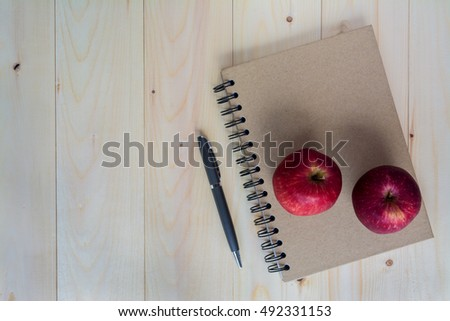 red apples on notebook and pen with light wooden background