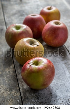 red apples on wooden table, natural light only - stock photo
