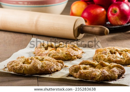 Red apples with apple tarts and rolling pin - stock photo