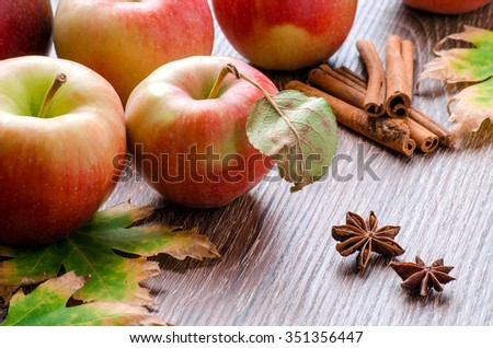 Red apples with leaves, cinnamon sticks, star anise and autumn leaves