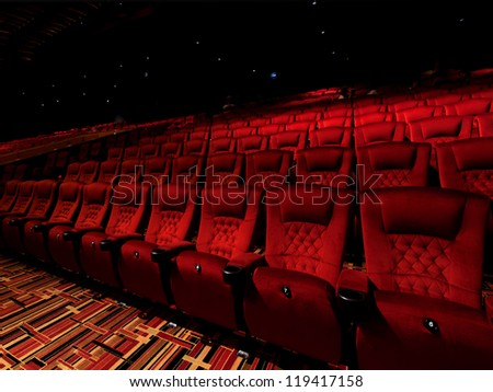 Red arm chair in dark theater - stock photo