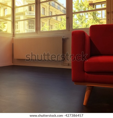 Red armchair in empty room with windows.