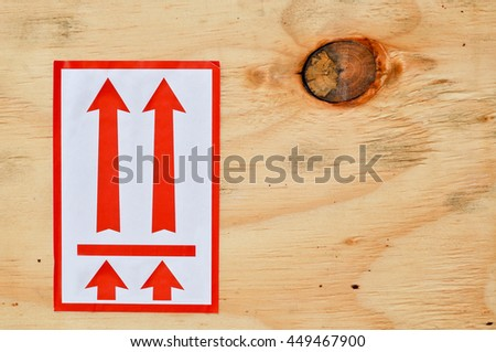 red arrow on plywood, it's a symbol that means to take up the top. - stock photo
