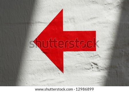 Red arrow on white wall with shadow - stock photo