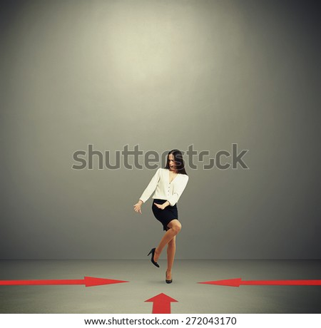 red arrows indicate at frightened woman in formal wear over dark grey background with empty copyspace overhead - stock photo