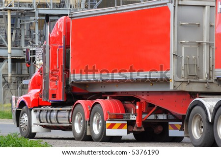 Red articulated semi truck - stock photo