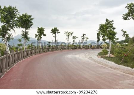 red asphalt road at sea - stock photo