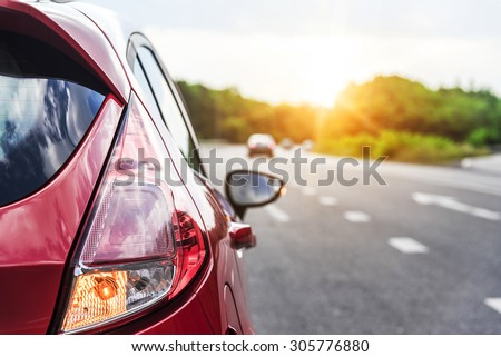 Red automobile on the road at sunset. Travel concept. - stock photo