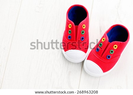 red baby shoes on white - baby stuff - stock photo