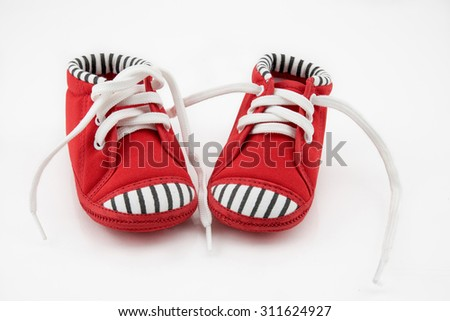 Red baby sneakers on white background