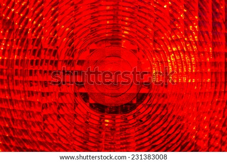 red background - detail of a red traffic warning lamp - stock photo