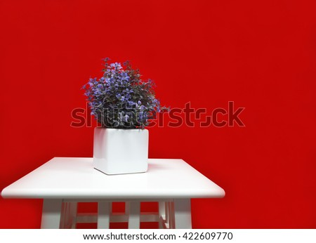 Red background with flowers on white chair - stock photo