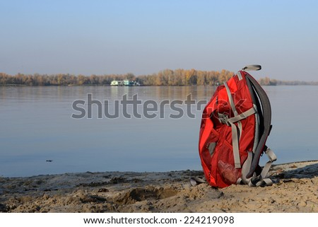 Red backpack on coast river  - stock photo