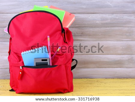Red bag with school equipment on wooden background - stock photo