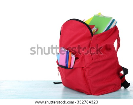 Red bag with school equipment on wooden table isolated on white - stock photo
