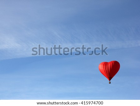 red balloon in the shape of red heart on a morning clear blue sky as a background