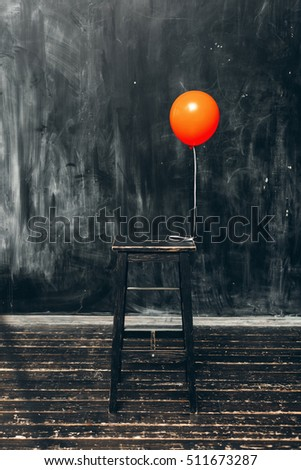 red balloon with chair on the background of black wall