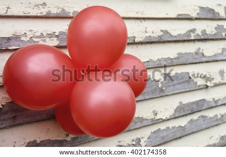 Red balloons on rustic paint peeling wall - stock photo