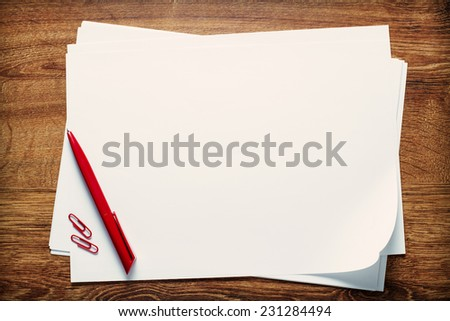 Red ballpoint pen and paperclips lying on a stack of blank sheets or pages of white paper with copyspace for your text on a wooden desk, view from above - stock photo