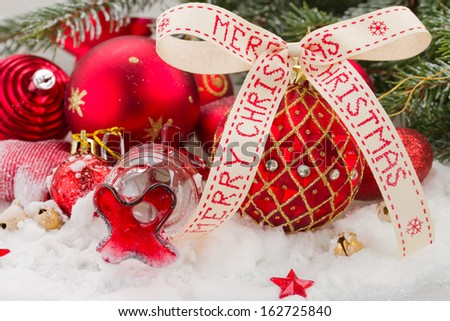 red balls for christmas in snow under evergreen  fir tree - stock photo