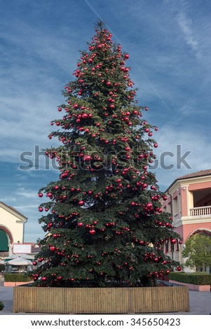 red balls on big christmas tree on blue sky background