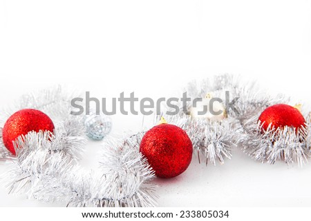 Red balls on silver tinsel. Isolated over white. - stock photo