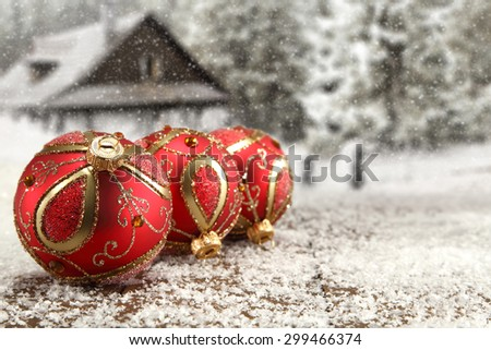 red balls on table and xmas time with shiny snow  - stock photo