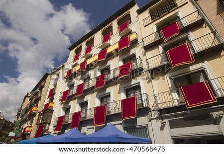 Red banners hang from windows of historical buildings in the Plaza de Zocodover in Toledo, Spain