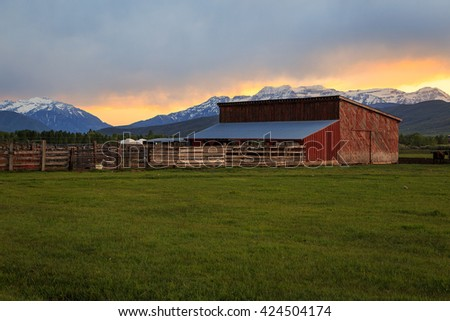 Red barn in a farm field, Heber Valley, Utah, USA. - stock photo