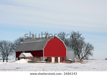 Red barn sits amid pure white snow on the flat plains