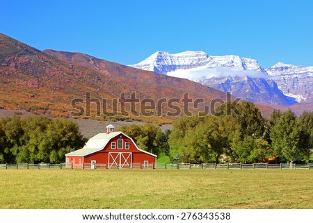 Red barn with fall colors in the background, Utah, USA. - stock photo