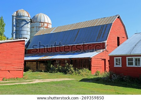 Red barn with silos on a dairy farm, Utah, USA. - stock photo
