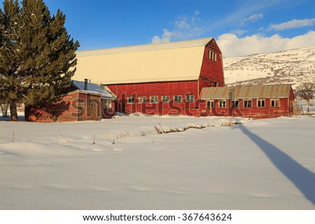 Red barn with snow in rural Utah, USA. - stock photo