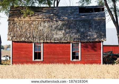 Red barns contrast nicely with golden wheat in the late day sun on this attractive farm. - stock photo