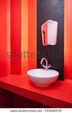 Red bathroom, wash basin and mirror - stock photo