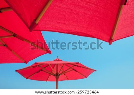 Red Beach umbrella against sunny blue sky. - stock photo