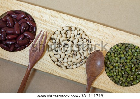 red beans and soy beans and green beans in wood tray with spoon and fork - stock photo