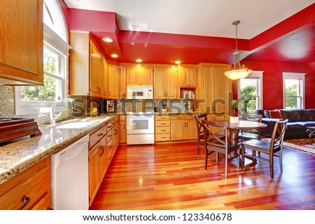 Red beautiful large kitchen with cherry hardwood. - stock photo